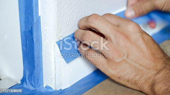 805500886 istock photo Painter Man Using Masking Blue Tape to Secure Baseboard, Moulding. Preparation For Room Painting. 1221308509
