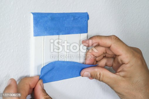 805500886 istock photo Painter Man Using Masking Blue Tape to Secure Light Switch. Preparation For Painting Room 1221306225