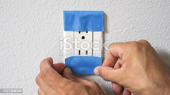 805500886 istock photo Painter Man Using Masking Blue Tape to Secure Power Outlet. Preparation For Room Painting. 1221306233