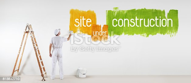 istock painter man with paint brush drawing under construction text isolated on the blank white wall 813842710