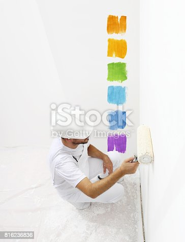 istock painter man with paint roller painting color samples, top from view isolated on blank white wall background 816236836
