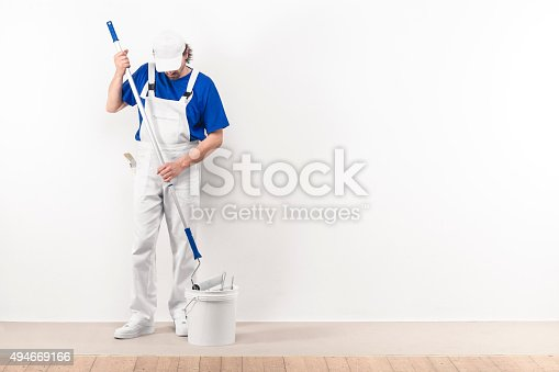 589454570 istock photo Painter mantakes color with paint roller from the bucket 494669166