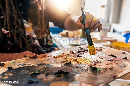 istock Painter mixes paint on the palette. Closeup 1053904658