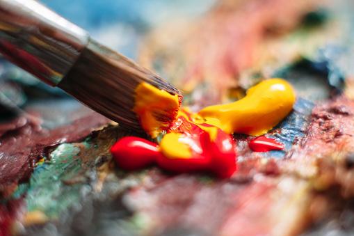 istock Painter mixes paint on the palette. Closeup 518845100