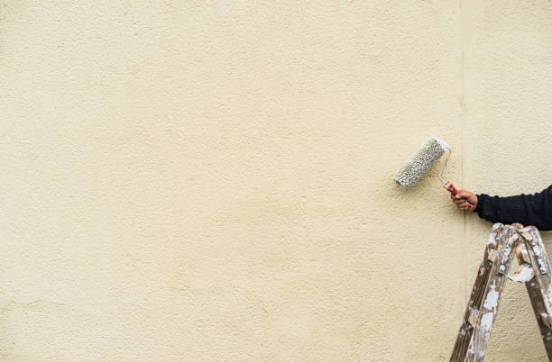 Peintre sur une échelle à le œuvre, peinture murale - Photo