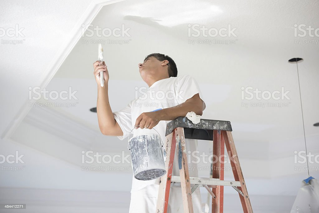 Painter painting a ceiling. stock photo