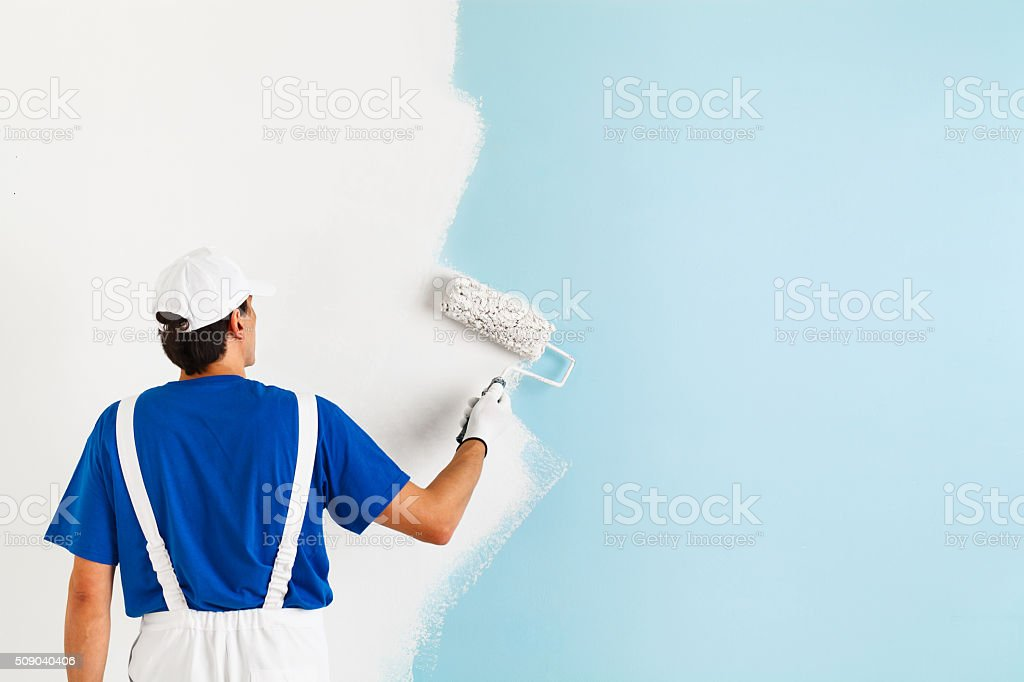 painter painting a wall with paint roller stock photo