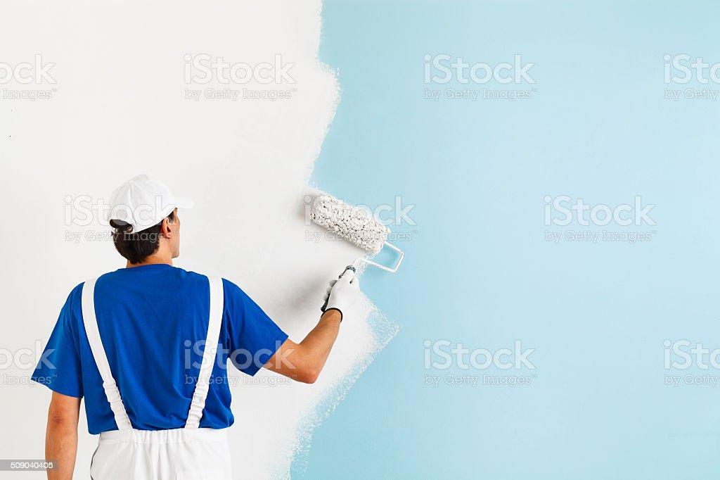 Artista pintando un muro con rodillo de pintura - foto de stock