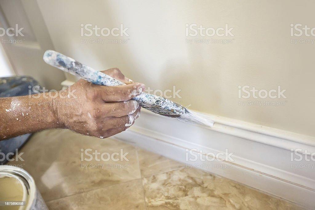 Painter painting baseboard molding royalty-free stock photo
