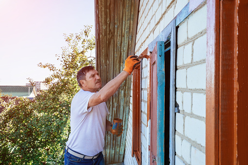 istock Painter painting the windows of a exterior house 1065914296