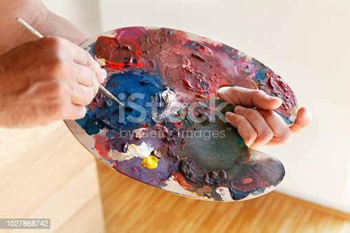 Painter holding paintbrush and palette with colors