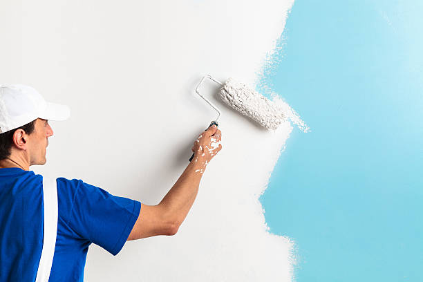 painter painting with paint roller - painting wall bildbanksfoton och bilder