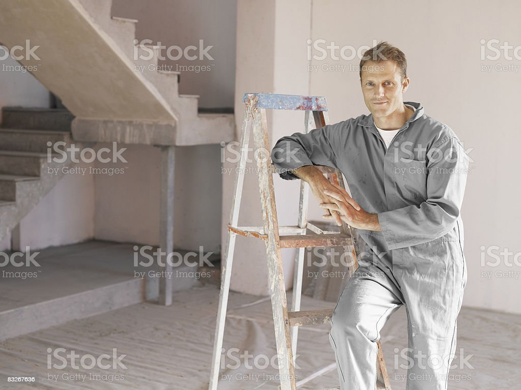 Painter posing with ladder in unfinished room stock photo
