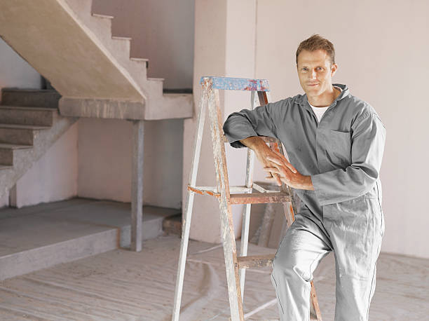 painter posing with ladder in unfinished room - painter stock photos and pictures