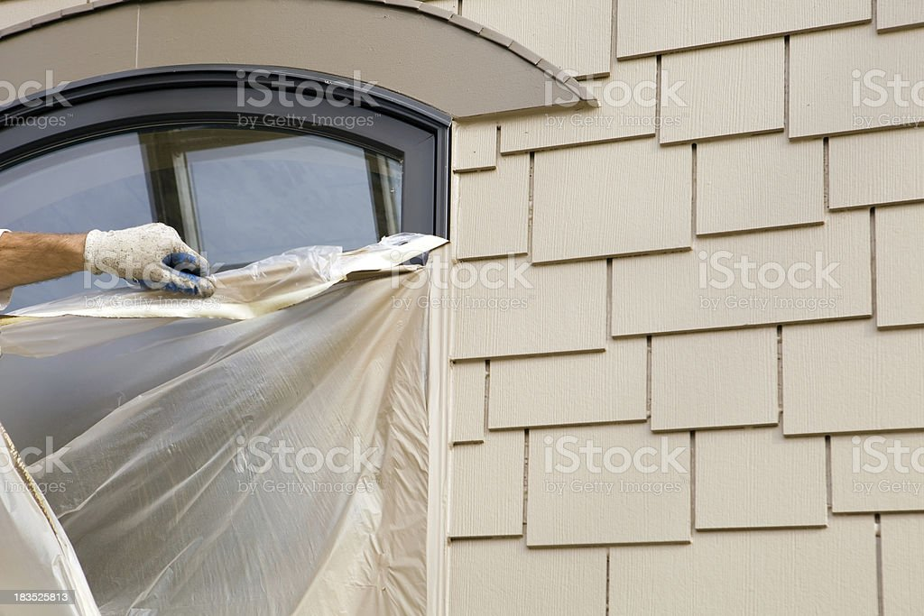 Painter Removing Plastic Masking from an Exterior Window stock photo