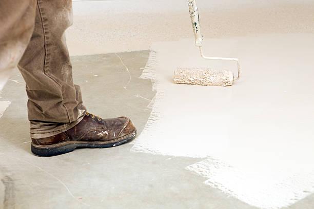 maler rolling epoxid- farbe auf beton-etage - diy beton stock-fotos und bilder