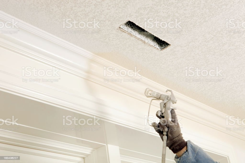 Painter Spraying Paint on Crown Moulding stock photo
