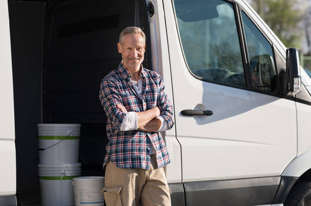 Painter standing against van Portrait of painter standing next to his van with paint container. Decorator standing next to van and looking at camera. Happy smiling worker leaning on his white truck with folded arms. commercial land vehicle stock pictures, royalty-free photos & images
