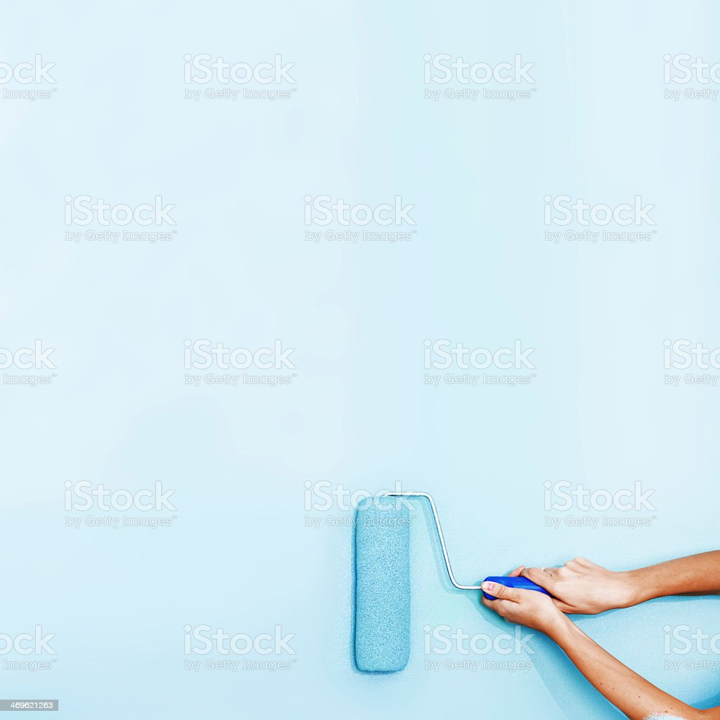 Painter using a roller brush painting a wall baby blue stock photo