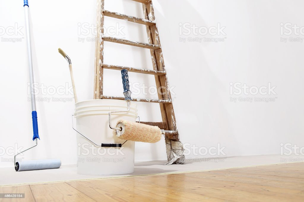 painter wall concept, ladder, bucket, roll paint on the floor stock photo