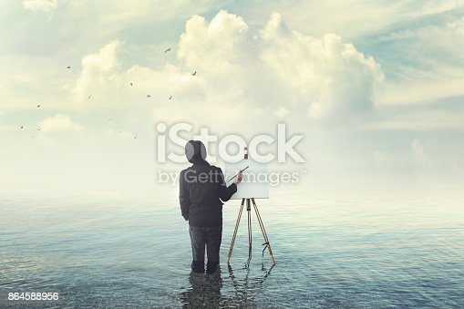 istock painter with brush with canvas easel finding insiration in water 864588956