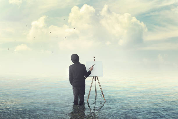painter with brush with canvas easel finding insiration in water stock photo