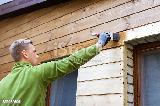 istock painter with paintbrush painting house wood facade 855082606