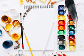 Painter workplace. Creative hobby. Empty sketchbook gouache watercolor palette on white background.
