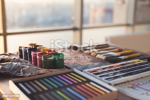 824254912 istock photo Painter workplace. Palette with brushstrokes and paintbrushes. Colorful gouache, crayons sets 695137898