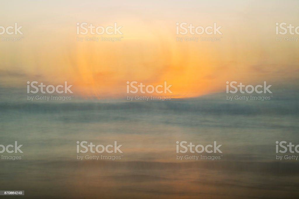 Painterly Muted Sunset over Ocean in Orange Blue and Gray stock photo