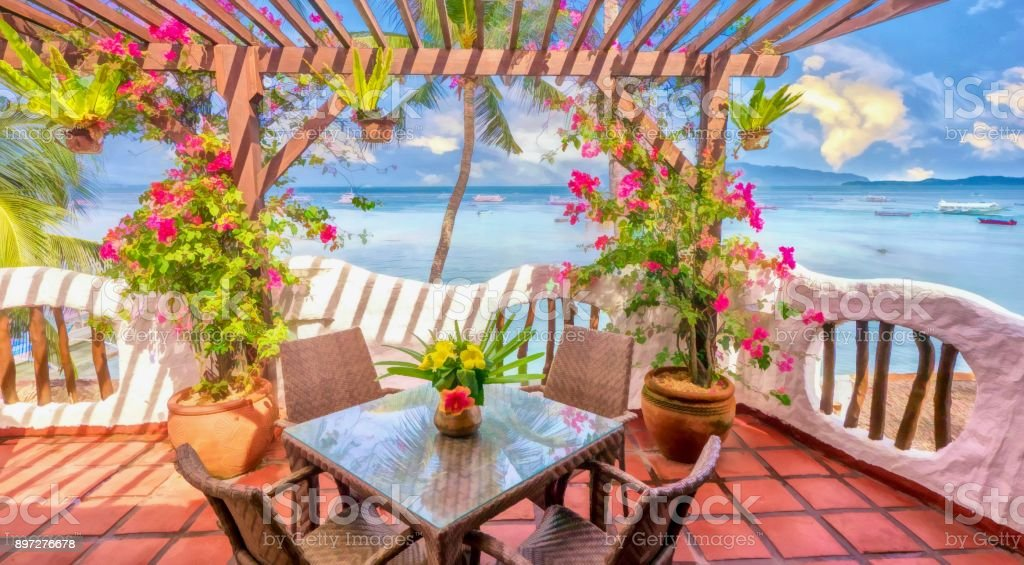 Painterly style photograph of a sunny whitewashed balcony with colorful bougainvillea flowers and terra-cotta tiles overlooking palm trees and turquoise water on a tropical island. stock photo