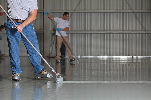 Painters Apply Epoxy Paint to an Airport Hanger stock photo