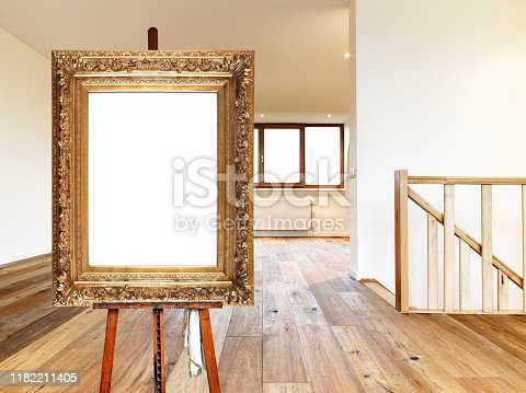 671393252 istock photo Painter's easel and empty antique golden frame in a modern interior 1182211405