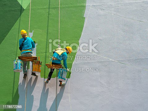 istock Painters painting exterior of building 1178572265