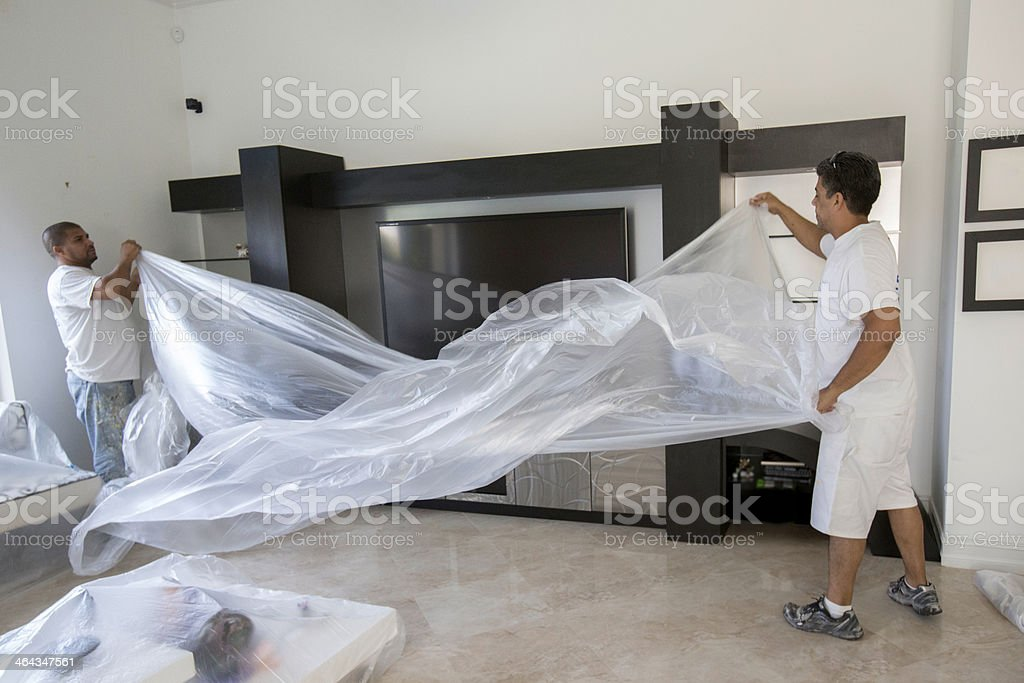 Painters preparing to cover furniture stock photo