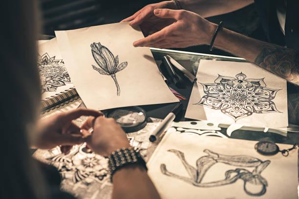 painters speaking about image in room - tattoo ideen stock-fotos und bilder