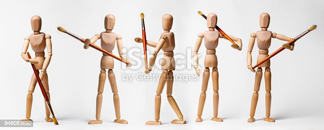 Painter's wooden models holding paintbrushe in different poses isolated on white