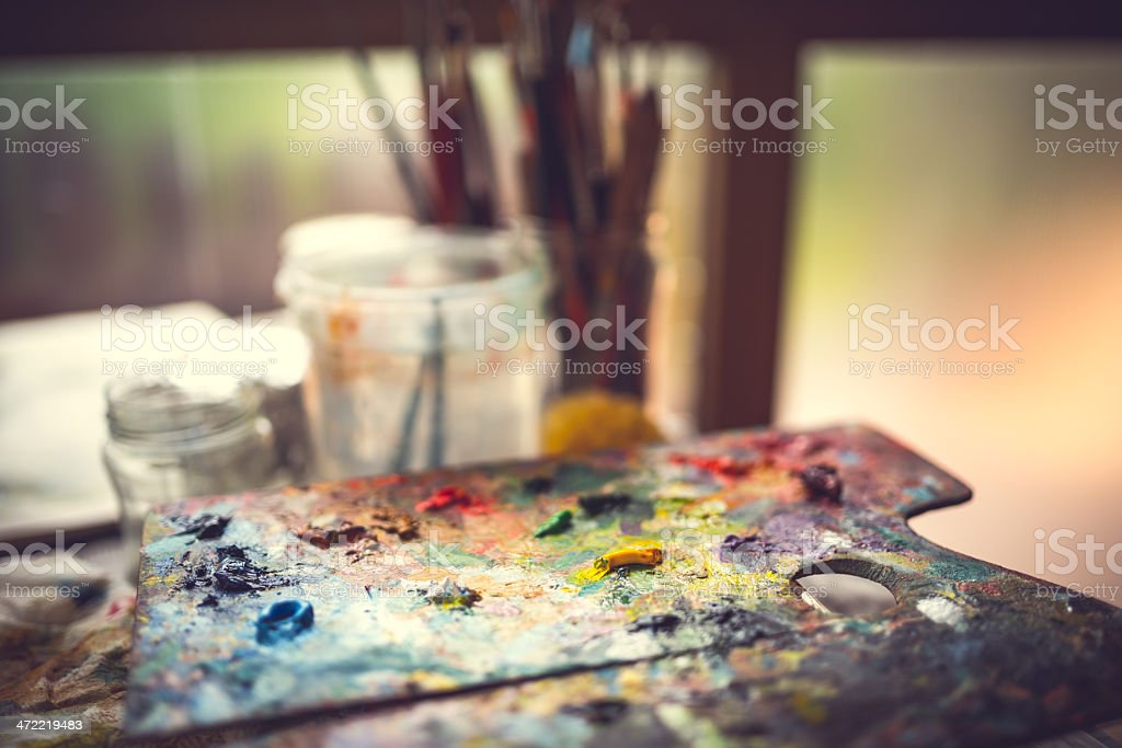 Paint-filled artists palette with brushes in the background stock photo