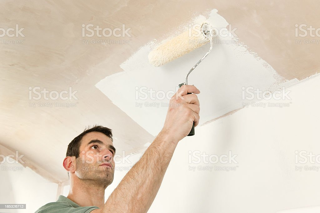 Painting a ceiling by roller stock photo
