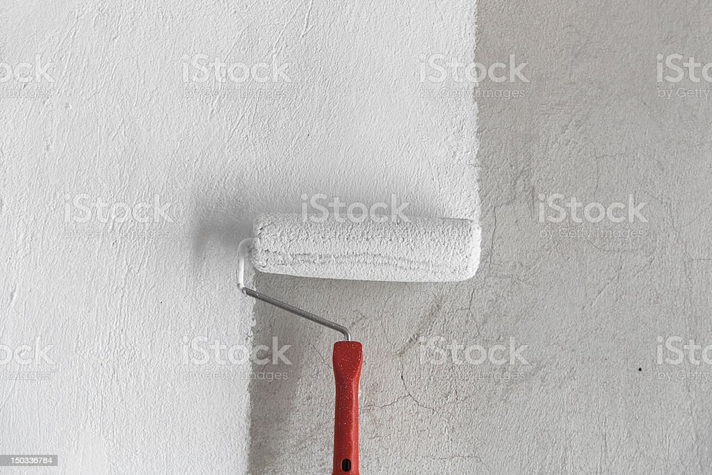 Painting a Rough Wall by Roller. stock photo