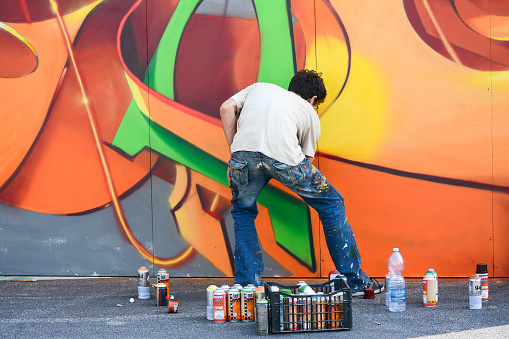 bologna,Italy-June 7,2014:young artist painting a wall in the middle of the day