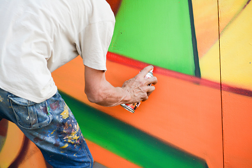 young artist painting a wall in the middle of the day