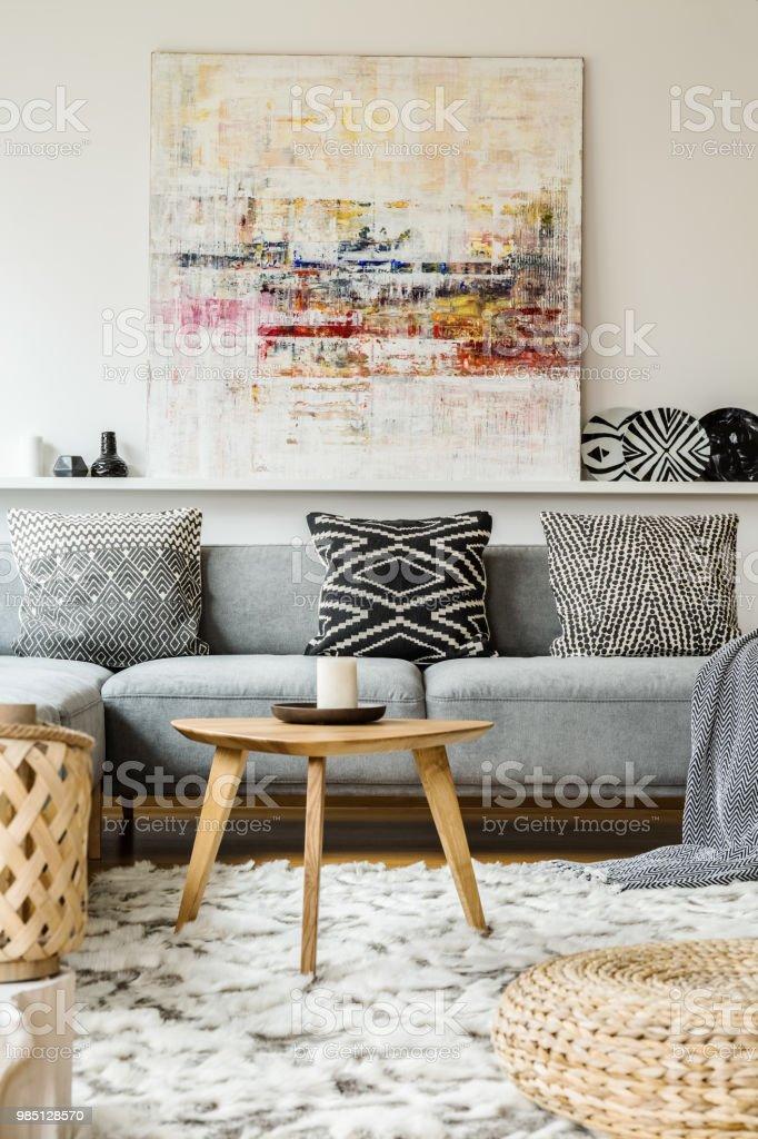Gemälde über Graue Couch Im Boho Wohnzimmer Interieur Mit Holztisch