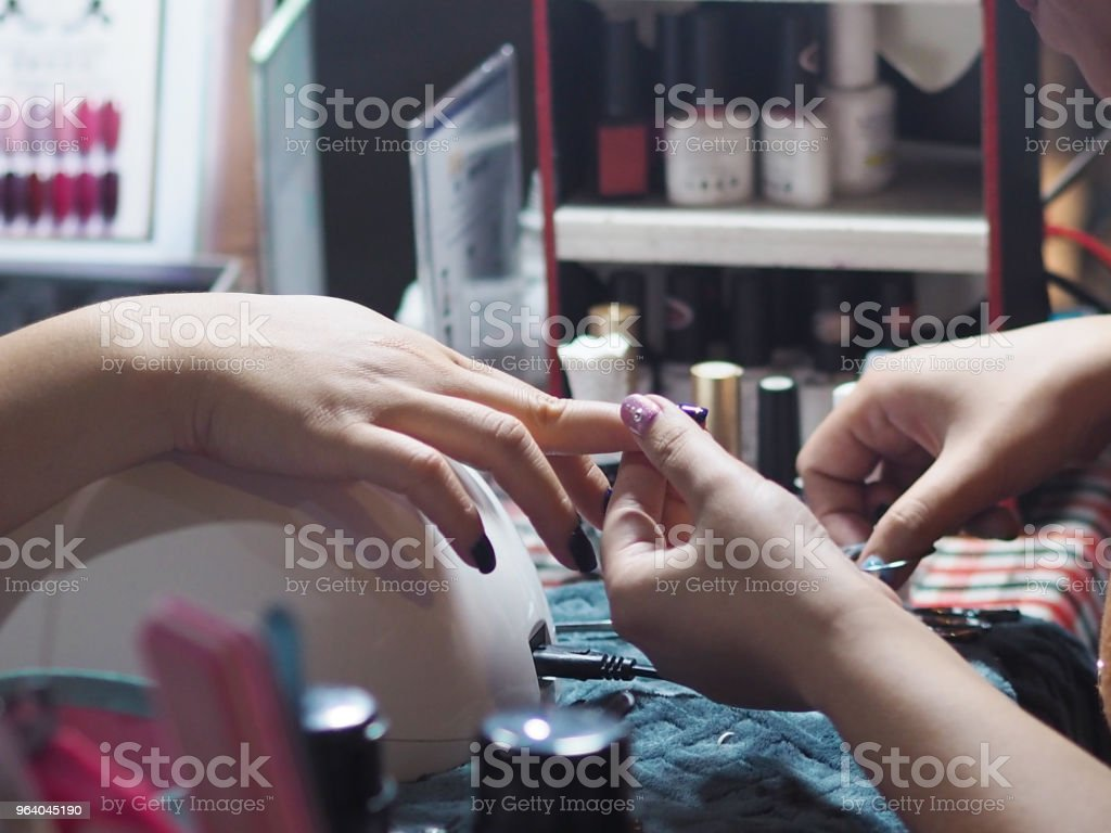 painting and decorating blue color on woman nails - Royalty-free Adult Stock Photo
