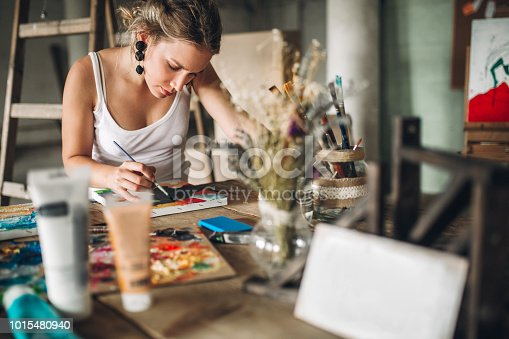 Beautiful young woman painting and drawing in her atelier - art studio