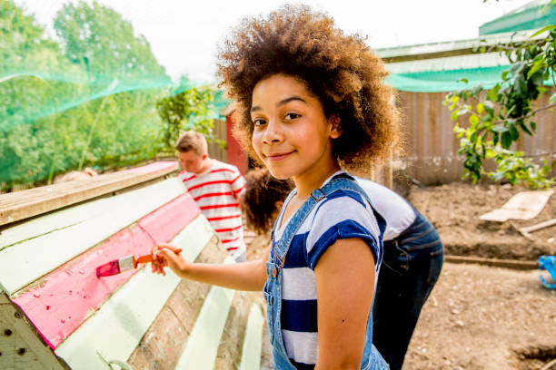 Painting at the Farm A young girl helps paint the chicken coop at the farm. community garden stock pictures, royalty-free photos & images