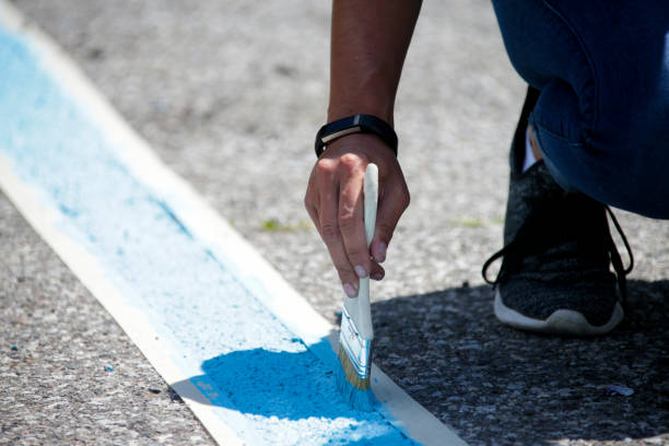 Painting blue parking lot lines by hand stock photo