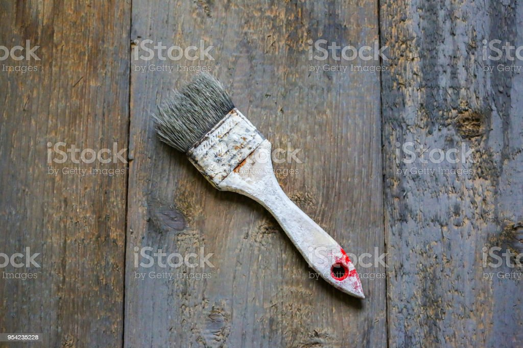 Painting brush in white paint dye is lying on the wooden background. Realistic grey and brown vintage surface. Shaggy and grained rough background for working purpose. stock photo