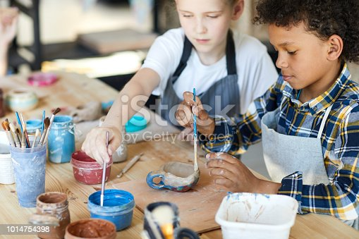 Two youthful claaamates sitting by table and painting self-made clay items at lesson