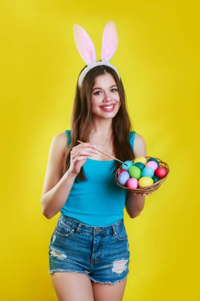 ei malen. . ostertag. kaninchenfrau. hasen kostüm. lächelnde frau mit häprigen ohren, die ei bemalen - osterhase zeichnen stock-fotos und bilder